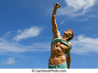 Happy fit man with his arm raised in joy, on blue sky...