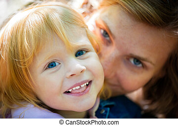 Mother playing with her daughter - outdoor shot