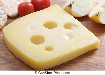 """Jarlsberg cheese on a board - A wedge of jarlsberg """"swiss""""..."""
