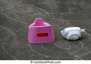 Potty trainning - A full diaper beside a pink potty outdoor.