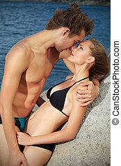 kiss on a beach - Beautiful young couple in love having...
