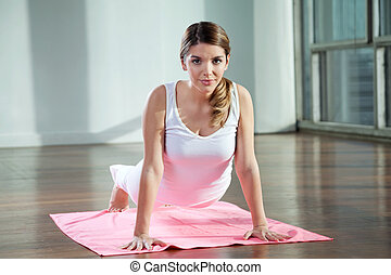 Woman Practicing Yoga On Mat - Portrait of a beautiful young...