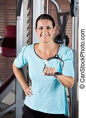 Woman Training On Machine In Gym