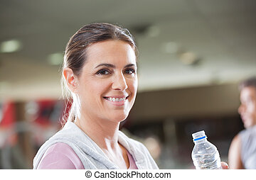 Woman Holding Bottle Of Water At Health Club - Portrait of...