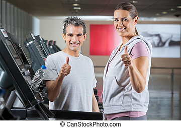 Instructor And Client Showing Thumbs Up Sign In Health Club