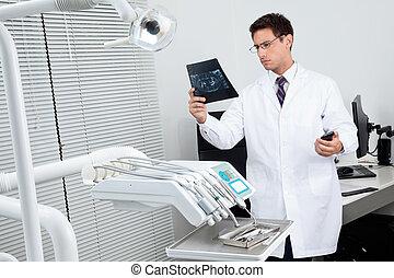 Dentist Analyzing X-Ray Report - Male dentist analyzing...