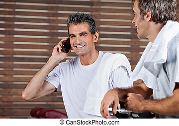 Man On Call While Friend Looking At Him In Health Club