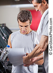 Instructor Making Notes - Male instructor making notes on...