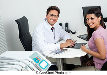 Happy Dentist And Patient At Office Desk - Portrait of happy...