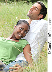 Mixed couple laying in a field