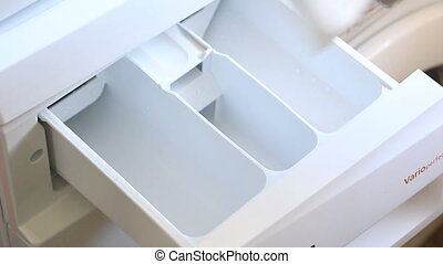 Washing powder and softener - Loading washing machine with...