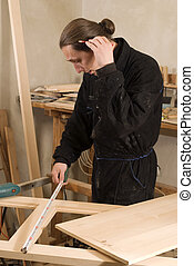 Carpenter working in his workshop with metre