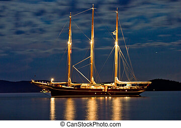 Wooden sailboat illuminated at night anchored