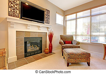 Fireplace with large TV above, elegant chair with windows.