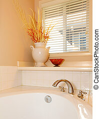 White tub with vase and window corner with beige wall.