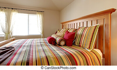 Large bed with beautiful bedding in stripe red, yellow and green.