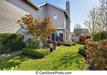 Nicely landscaped back yard with house during spring in...