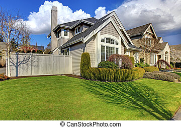 Classic American house with fence and green grass during spring.