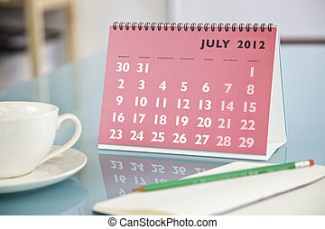 July - Desktop calendar sitting on a glass desk showing the...