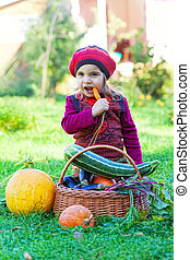 little girl sits on a grass near to a basket with vegetables...