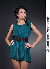 Fashion model brunette woman in evening dress over dark