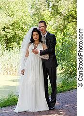 groom with the bride walk in a summer garden