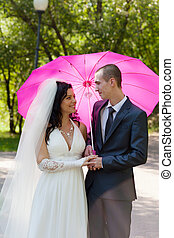 Newly-married couple in a summer garden under a pink...