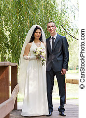 groom and the bride cost on the wooden bridge in a summer...