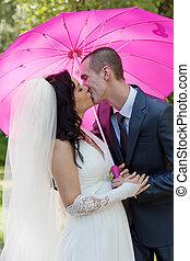 groom and  bride kiss under a pink umbrella