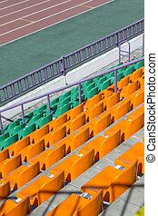rows of plastic seats at stadium