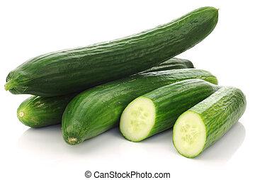 fresh cucumbers - three fresh cucumbers and a cut one on a...