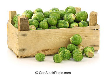 freshly harvested brussel sprouts in a wooden crate on a...