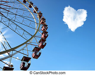 Cloud in the form of hearts and a Ferris wheel on the blue...