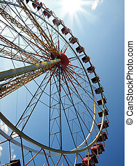 Ferris wheel in the background of blue sky and sun