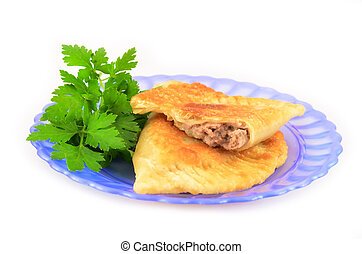Pasties with meat on a plate decorated with parsley