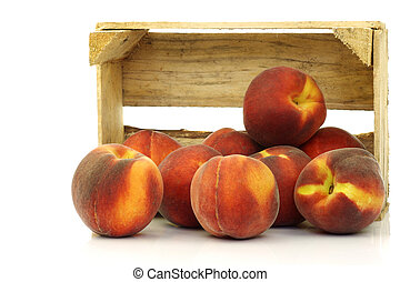 freshly harvested peaches in a wooden crate on a white...