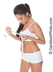 Shapely woman measuring her breast with a tape. Isolated on...