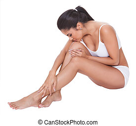 Beautiful barefoot woman sitting on the floor with her long...