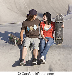 Kids at skatepark - Teen couple hangs out at a skatepark