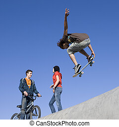 Tricks at skatepark - Kids hang out and do tricks at the...