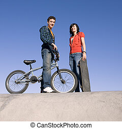 Teen couple at skatepark - Teens with a bike and skateboard...