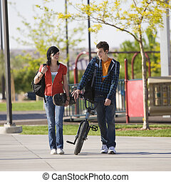 Teens couple walks - Teen couple walks through park