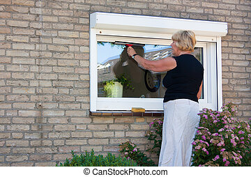 Woman washing small window - Dutch retired senior Woman...
