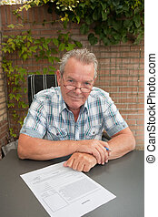 Senior about to sign legal document in his backyard