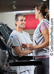 Instructor Looking At Female Client Exercising On Treadmill