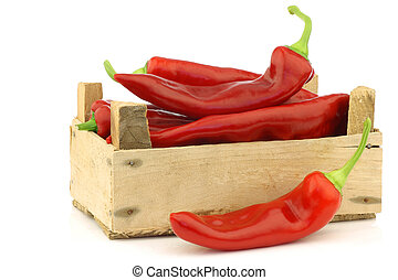 fresh red sweet peppers (capsicum) in a wooden crate on a...