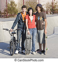 Three teens at skatepark - Three kids hang out at the...