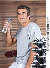 Happy Man Drinking Water From Bottle At Health Club -...