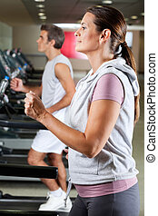 People Running On Treadmill - Profile shot of mature woman...