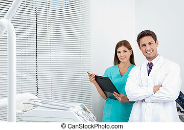 Doctor And Female Assistant In Dental Clinic - Portrait of...